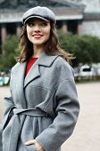 Lifestyle and people concept: portrait of young woman in elegant gray coat standing on the street in poster
