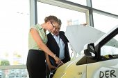 Woman buying a car in dealership looking under the hood at the engine