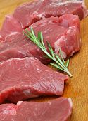 Raw boneless lamb meat steaks on wooden chopping board.