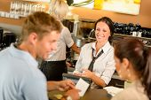 Couple paying bill at cafe cash desk smiling waitress bar