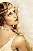 Retro posing lady with antique fan and flapper dress headband