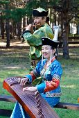 ULAN-UDE, RUSSIA - SEPTEMBER 13: Unidentified man and woman playing on the Buryat instruments. Costu