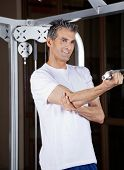 Happy mature man working out in fitness center