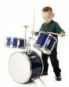 A young preschooler intently drumming on a child-sized drum set.  On a white background.  (Motion bl