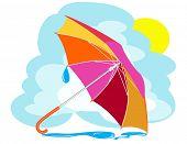 Color umbrella with rain drops against the sky