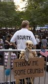 NEW YORK - SEPT 17: A security guard behind a sign that reads 'Throw Me Some Crumbs' in Zuccotti Par