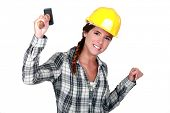 Happy female worker holding hammer