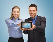 picture of two business people showing tablet pc with graph