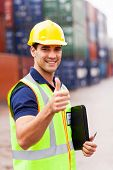 handsome young container warehouse worker giving thumb up at the harbor