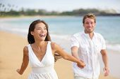 Beach couple running having fun laughing together during summer travel vacation holiday on beautiful