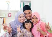 Happy Asian family at home. Muslim family showing v victory hand sign and having fun. Southeast Asia