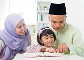 Malay Muslim parents teaching child reading a book. Southeast Asian family at home.