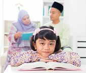 Muslim girl reading book. Malay family at home. Southeast Asian parents and child living lifestyle.
