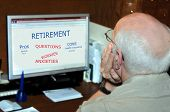 "stock photo of pro-life  - ""Pros and Cons of retirement"" are shown on home computer screen. Older man holds his head and stares at screen. - JPG"