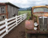 image of chicken-wire  - old truck on a farm with fence rooster and a chicken coop with clouds and mountains in background - JPG