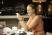 Young woman chatting on smartphone in cafe.