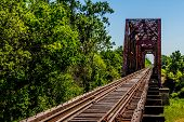 stock photo of trestle bridge  - An Interesting Side Angled View of an Old Railroad Trestle with an Old Iconic Iron Truss Bridge Over the Brazos River - JPG