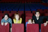 Four young scared friends see movie in cinema theater. Girl hides behind chair.