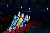 Four happy friends leaned over backs of chairs and look at screen in cinema theater.