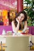 Young woman in a cafe or ice cream parlor eating a cake and using her phone, maybe she is single or