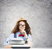 Young funny woman in glasses using typewriter