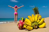 foto of idealistic  - Tropical fruits and a woman in a bikini sunbathing on the beach on sea background - JPG