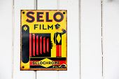 NR SOUTHAMPTON,UK - 25 June 2013: Old style tin advertising board for Selo film displayed on painted wood with space for text. On 25 June 2013 Near Southampton UK
