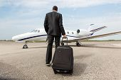 stock photo of jet  - Rear view of businessman with luggage walking towards corporate jet - JPG