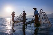 stock photo of fisherman  - Silhouette of traditional fishermans in wooden boat using a coop - JPG