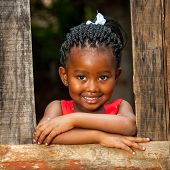 Little African Girl Leaning On Wooden Fence.
