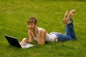 Happy Young Woman With Notebook And Mobile Phone On The Grass