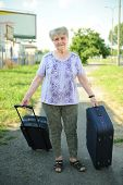 Senior woman with suitcases