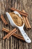 Ground cinnamon spice ,and five pieces of cinnamon barks, old wood background