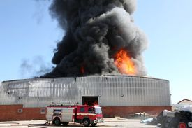 image of firemen  - Warehouse building burning with intense flames and firemen attending - JPG