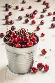 Little Brass Bucket Of Cherries On A Table