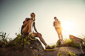 Two hikers with backpacks relaxing on a rocky hill and enjoying sunset