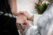 stock photo of youg  - Priest holding hand blessing youg couple at a wedding ceremony - JPG