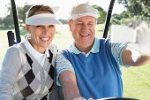 Happy golfing couple sitting in golf buggy taking a selfie on a sunny day at the golf course