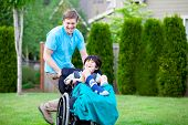 stock photo of babysitting  - Father running with disabled son in wheelchair - JPG