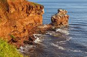 The rocky shore of Prince Edward Island at daybreak illuminating the cliffs and rocks bright red. A
