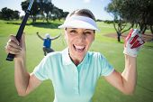 Lady golfer cheering at camera with partner behind on a sunny day at the golf course