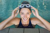 Fit swimmer smiling up at camera in the swimming pool at the leisure center
