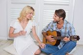 pic of serenade  - Handsome man serenading his girlfriend with guitar at home in the living room - JPG