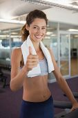 Fit woman wearing towel around shoulders showing thumbs up at the gym