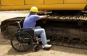 picture of backhoe  - disabled man working on the tracks of a large backhoe - JPG