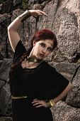 stock photo of tunic  - Beautiful makeup girl wearing black tunic and an antique jewels rocky wall on background - JPG