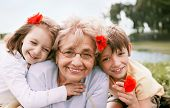 image of granddaughters  - Closeup summer portrait of happy grandmother with grandchildren outdoors - JPG