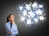 Thinking businesswoman looking at clouds of shining puzzle pieces