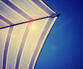 underside of a colorful beach umbrella against the sun in the sky done with a retro vintage instagr