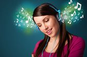 Pretty young woman with headphones listening to music, glowing notes concept